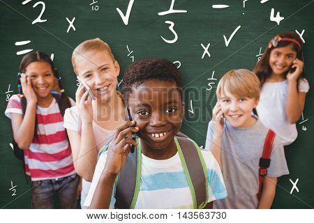 School kids using cellphones in school corridor against green chalkboard
