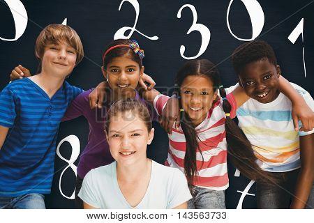 Happy children forming huddle at park against blackboard