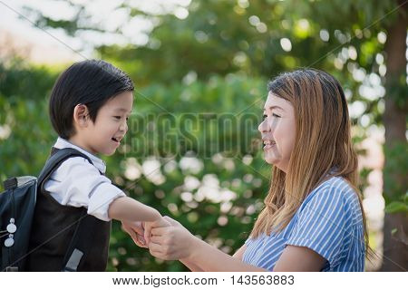 Asian mother saying goodbye to her son as he leave for Schoolback to school concept