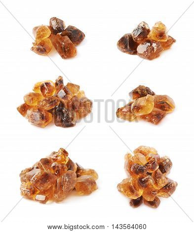 Pile of brown rock sugar crystals isolated over the white background, set of six different foreshortenings