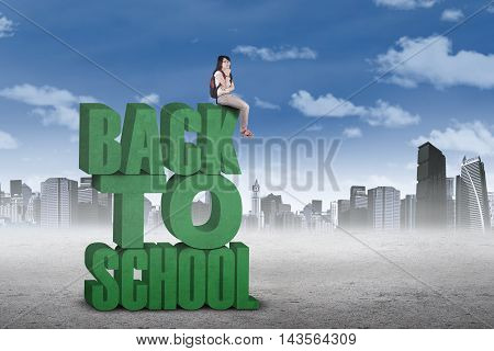 High school student carrying backpack and sitting on the text of back to school