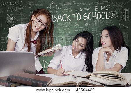 Female high school students back to school and doing school assignment together in the classroom