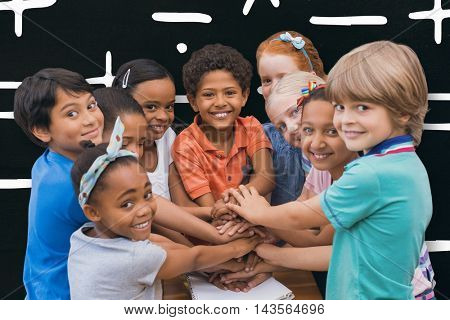 Cute pupils smiling at camera in classroom against black