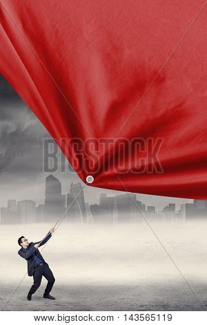 Male worker pulls a big red banner while wearing business suit