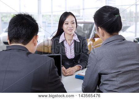 Portrait of two employers interviewing a young applicant on the car showroom