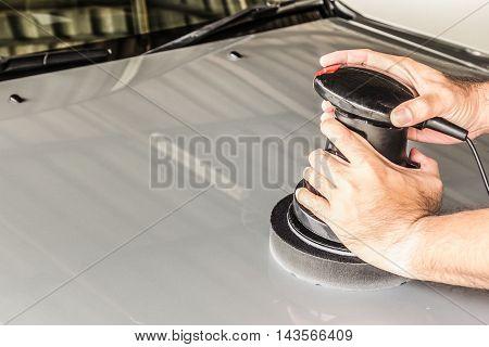 a man polishing the silver car with polisher machine