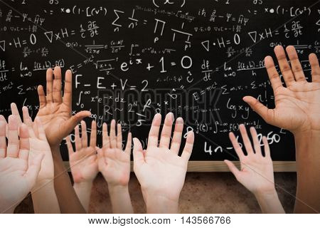 Hands raising in the air against blackboard on wall