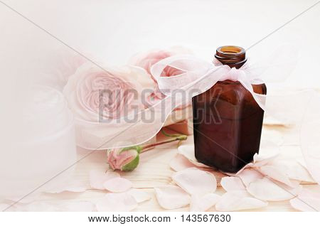 Bottle of perfume rose scent, decorated pink bow. Feminine beauty care toiletries. Pastel toned flower and petals, natural blurred background space.