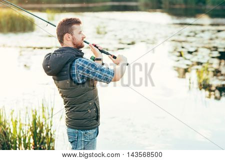 Fisherman with a spinning rod catching fish on a river. Man on a weekend. Hobby, leisure and active summer and autumn concept. Water background.