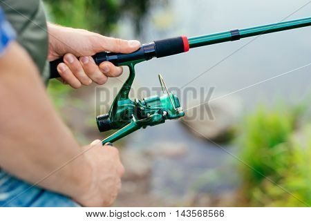Fisherman with a spinning rod catching fish on a river. Man on a weekend. Hobby, leisure and active summer and autumn concept. Nature background.