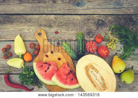 Fruits, vegetables on wooden background. Toned image.