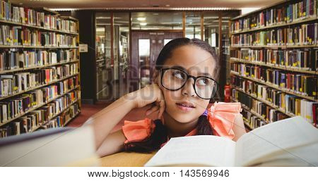 Young girl day dreaming by book at table against entrance of the college library