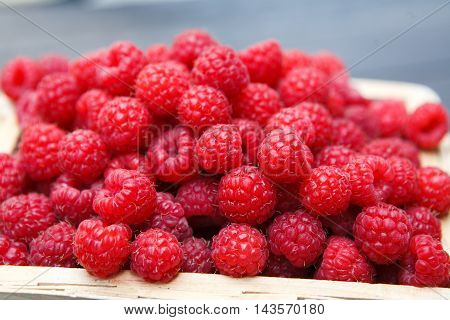 Wicker basket full of raspberries closeup. Heap of berries, summer harvest time