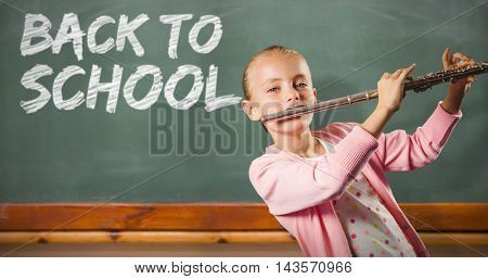 Girl playing the flute against blackboard