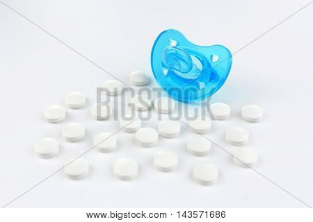 Baby pacifier with pills on white background