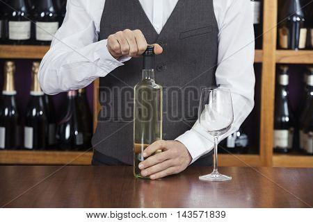 Bartender Opening Wine Bottle In Winery