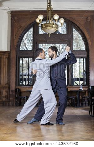 Partners Performing Argentine Tango In Restaurant