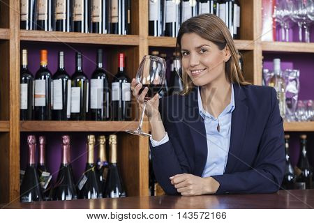 Female Customer Holding Red Wine Glass At Counter