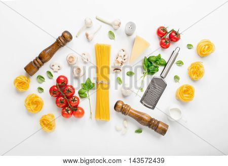 Fettuccine and spaghetti with ingredients for cooking Italian pasta on a white background top view. Flat lay