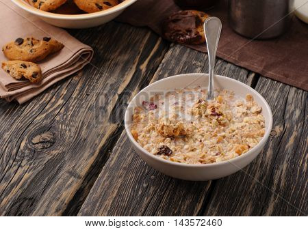 Oatmeal porridge in white bowl with spoon on a dark rustic table close up with copy space
