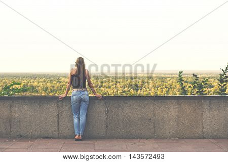 Romantic woman looking into the distance on a beautiful landscape standing on the viewing platform at sunset
