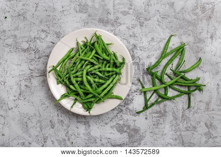 Fresh French bean in white plate on the rough light surface top view