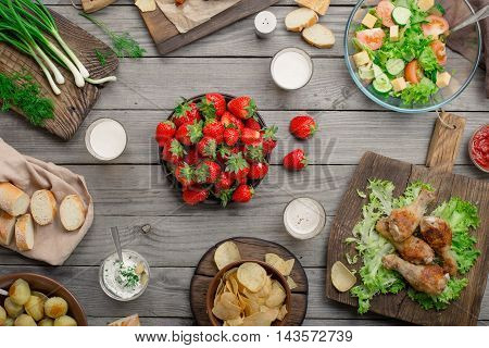 Outdoors Food Concept. On the wooden table different food grilled chicken legs bread salad potatoes potato chips beer and strawberry