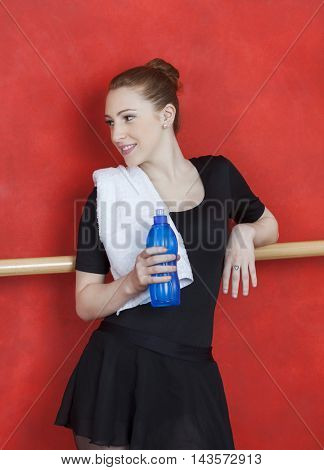 Ballerina Holding Waterbottle Against Red Wall