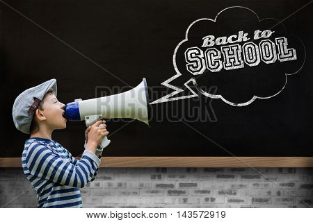Boy speaking on megaphone against blackboard on wall