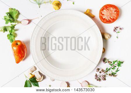 Various vegetables and seasoning cooking ingredients around blank plate
