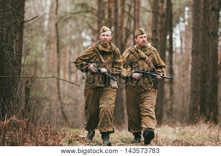 Pribor, Belarus - April, 04, 2015: Two unidentified re-enactors dressed as Russian Soviet soldiers in camouflage walks through forest