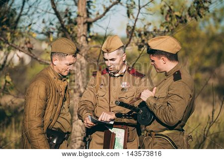 Teryuha, Belarus - October 3, 2015: Group of unidentified re-enactors dressed as Soviet russian soldiers scouts looking map of the area outdoor