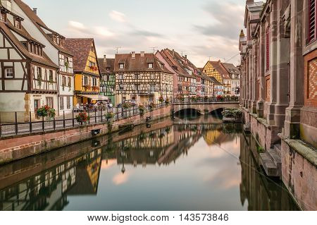 COLMAR FRANCE - 30TH JULY 2016: A view of colourful timber framed buildings along Little Venice in Colmar. Reflections can be seen in the River Lauch
