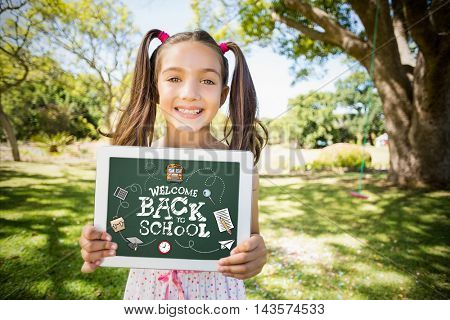 back to school against portrait of young girl holding digital tablet