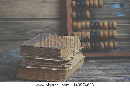 Old books and wooden abacus on the table