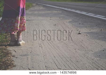 Girl with red backpack  stands on the road