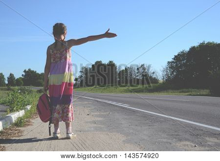 Little girl with red backpack travels hitchhiking