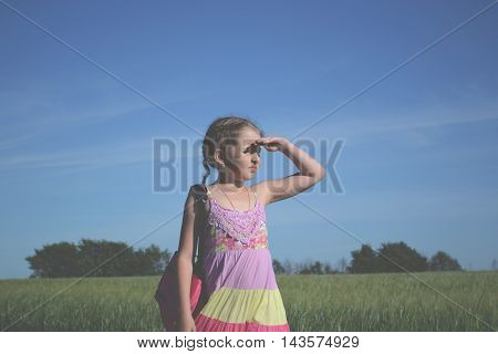 Little girl with backpack looks into the distance