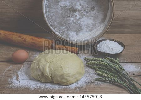 Cereals flour and dough on wooden background