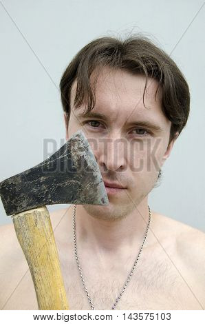 Portrait of young man with axe on gray background