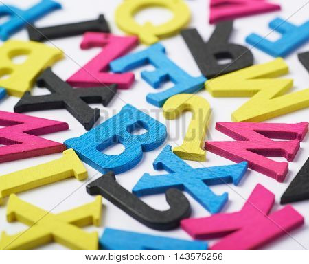 White surface covered with the multiple colorful cmyk painted wooden letters as a backdrop composition