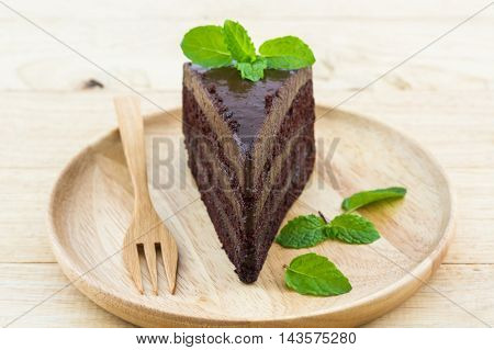 Chocolate cake slice in wooden plate on wood background.