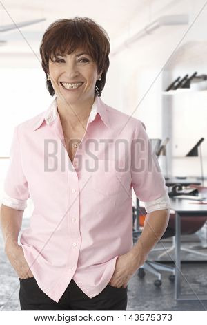 Portrait of happy mature woman standing hands in pockets, smiling.