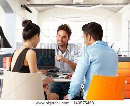 Young businesspeople working together, sitting at desk.