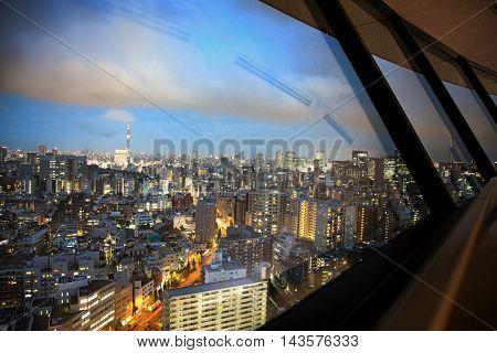 Tokyo cityscape during blue hour, as seen through a window.