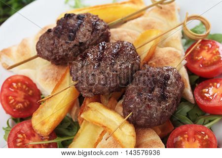Kofta kebab, oriental minced meat skewer with salad and french fries