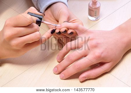 Closeup shot of woman in a nail salon. Receiving a manicure by a beautician.