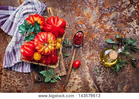 Ripe tomatoes, olive oil and basil. Selective focus, top view