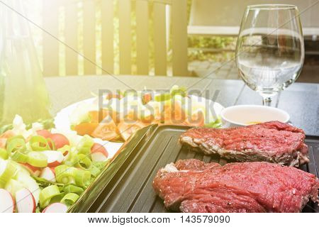 Beef steaks are grilled on an electric stove. Empty glass is in the background. All is in the sunshine.