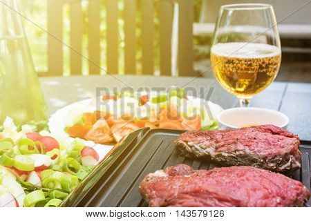 Grill steaks are on an electric stove. Bottle with oil various kinds of vegetables and glass of beer are standing on the table in the sunshine.